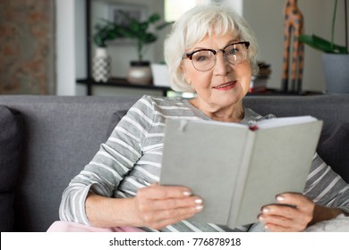 Portrait of grey-haired adult lady sitting on sofa while reviewing pictures. She is calm and pensive while relaxing at cozy home