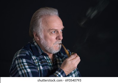 Portrait of a grey-haired, bearded Caucasian senior with tobacco pipe
