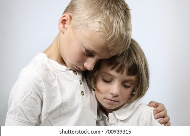 Portrait of grieving young children in an embrace