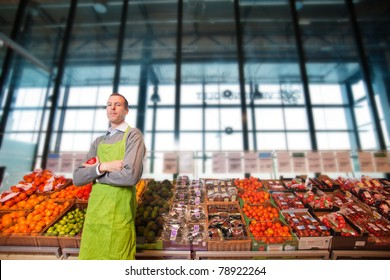 Portrait of a grocery store clkerk or owner in front of a vegetable counter