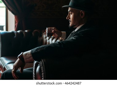 portrait of groom in hat sitting on the sofa with the glass of whiskey in luxury apartments
