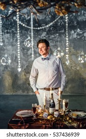 Portrait of a groom on the background decorated wedding table. Wedding decor, candles, candlesticks round balls.