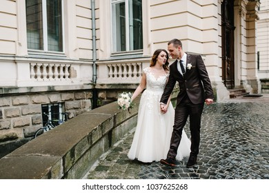 Portrait the groom in wedding suit and the bride in dress walking near ancient restored architecture, old building, old house outside, vintage palace outdoor.