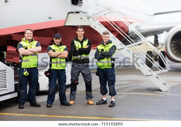Portrait Of Ground Team Standing Arms Crossed Against Airplane