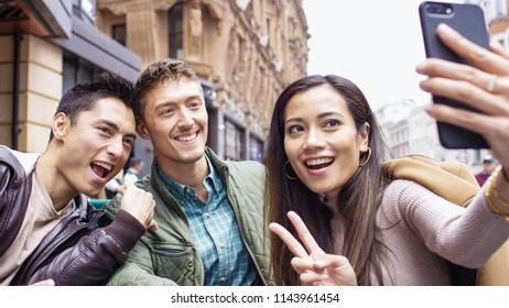 Portrait of a group of asian friends together in the city posing for a selfie