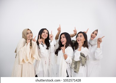 Portrait of a group of beautiful muslim female friends smiling with a free space. pointing up