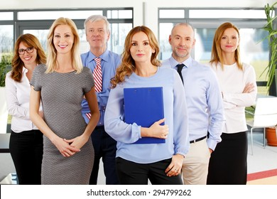 Portrait of group of business people in a row. Businesswomen and businessmen standing at office. Focus is on the woman in front.