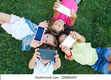 Portrait of group of childrens taking a selfie in the park.