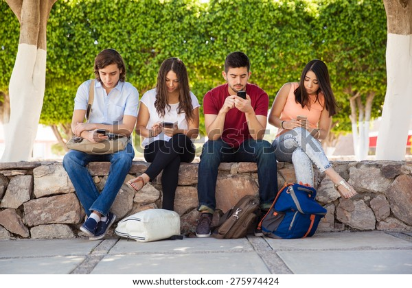 Portrait of a group of college students ignoring each other and using their smartphones at school