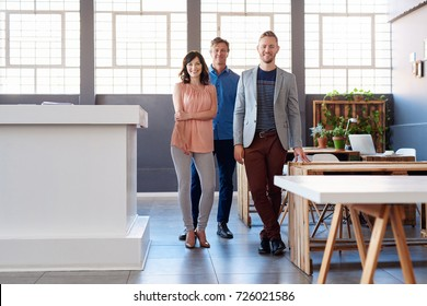 Portrait of a group of confident work colleagues smiling while standing together in a large modern office
