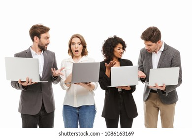 Portrait of a group of confused multiracial business people holding laptop computers isolated over white background