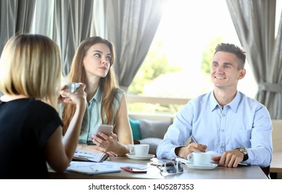 Portrait of group corporate people speaking and sitting in cafe. Man looking at gorgeous female business partners with smile. Young businesswoman holding smartphone looking away. Restaurant interior