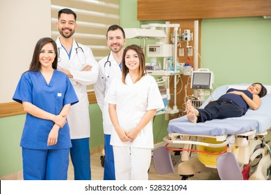 Portrait of a group of four doctors and nurses standing in a hospital room with a patient and smiling