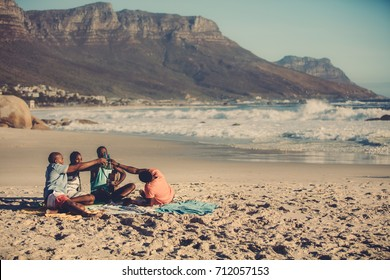 Portrait of group of friends playing guitar and drinking beer. People on the beach having a party.