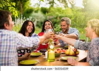 Portrait of a group of friends sitting on a terrace in the summer to share a meal, they  toast together with their glasses. Shot with flare