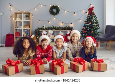Portrait of a group of happy smiling diverse children lying on the floor near Christmas presents tied with beautiful red bows and looking at camera. Children pose in a room with Christmas decorations.