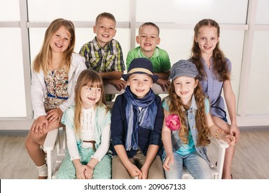 Portrait of group of kids sitting on the couch at home, hugging, smiling and laughing