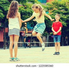 Portrait of group kids skipping on elastic jumping rope outdoor in summer time