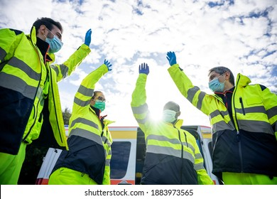 Portrait of a group of paramedics at the end of their shift in front of the ambulance while they high-fives in the air dressed in uniform and wearing a mask for protection from Coronavirus, Covid-19