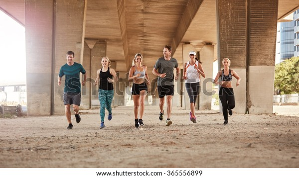Portrait of group of runners from running club under a bridge. Young men and women jogging together.