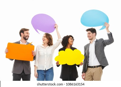 Portrait of a group of smiling multiracial business people holding empty speech bubbles isolated over white background