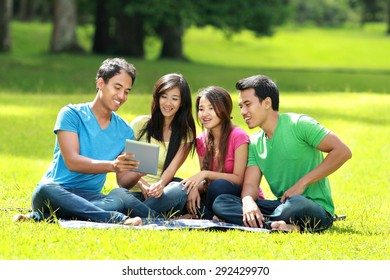 Portrait of Group of students studying in the park using tablet PC
