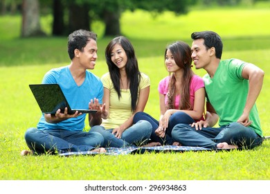 portrait of Group of students studying in the park using laptop computer
