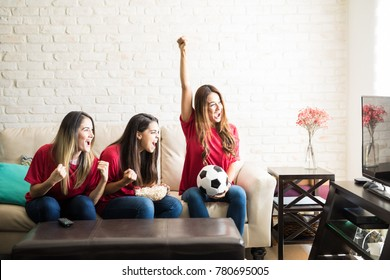 Portrait of a group of three female friends watching a soccer game on tv and celebrating a goal
