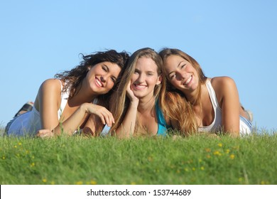 Portrait of a group of three happy teenager girls smiling lying on the grass with the sky in the background