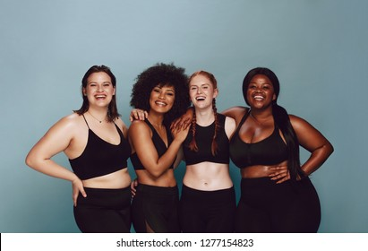 e460fc77c1f09 Portrait of group of women posing together in sportswear against a gray  background. Multiracial females. Fashion girl in sportswear on yellow  background