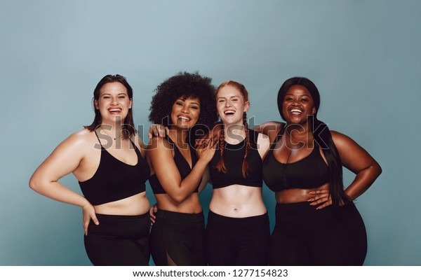 Portrait of group of women posing together in sportswear against a gray background. Multiracial females with different size standing together looking at camera and smiling.