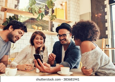 Portrait of a group of young friends meeting in a cafe and looking at the photos on mobile phone. Young men and women sitting at cafe table and using smart phone