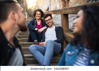 A portrait of group of young friends sitting outdoors on staircase in town.