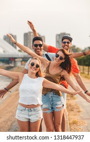 Portrait of group of young friends standing by the river in the city with arms outstretched and looking at camera.