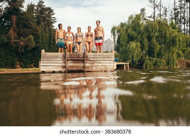 Portrait of group of young people standing on the edge of the pier on the lake. Young friends standing in a row on jetty.