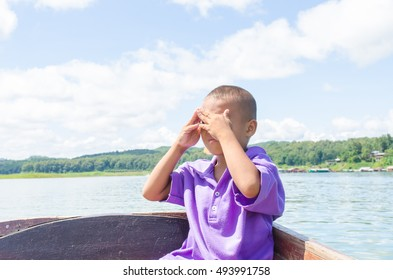 portrait of guide child on a wooden boat tours in the bright sun covering face by hand