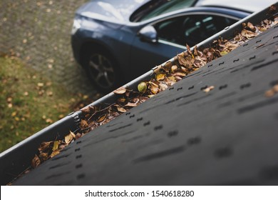 A portrait of a gutter and a slate roof of a house filled with fallen leaves due to autumn. The gutter needs to be cleaned during fall. In the background there is the driveway with a car on it.