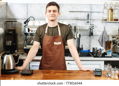 The portrait of the guy baristas at workplace on background of coffee