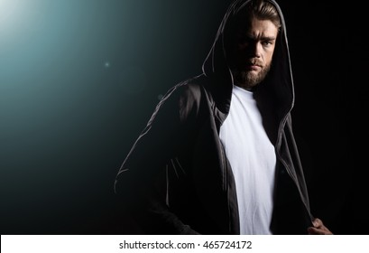 Portrait of a guy in blank t-shirt on a black background  in a ray of light