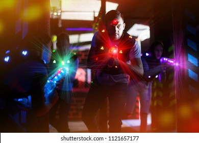 Portrait of guy in colored beams of laser guns during laser tag game on dark arena