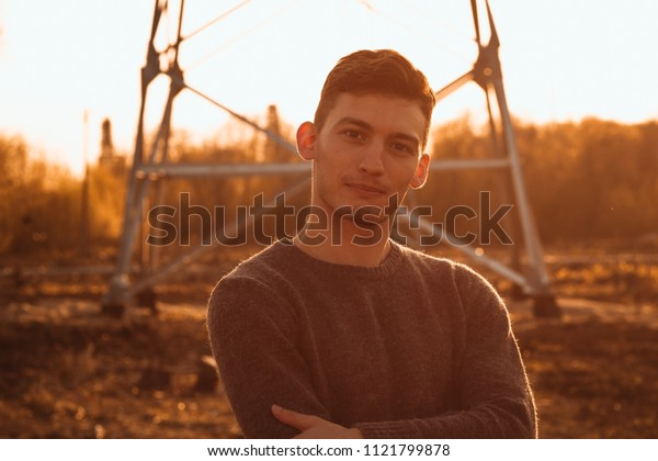 portrait of a guy in the field on a sunset background.