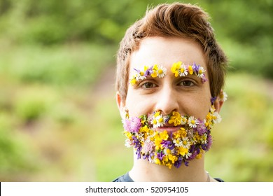 portrait of a guy with flowers instead of his beard relaxed in the nature