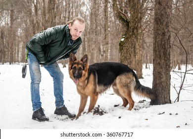 Portrait of guy with his german shepherd in winter forest