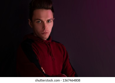 Portrait of a guy in a hooded sweater. Close up using red backlight.