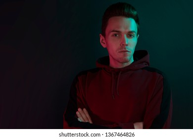 Portrait of a guy in a hoodie. Close-up, using green and red back lights.