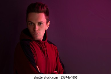 Portrait of a guy in a hoodie in the studio. Close up using red backlight.