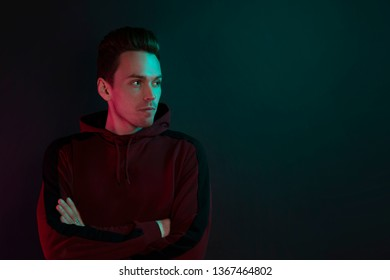 Portrait of a guy in a hoodie without looking at the camera. Close-up, using green and red back lights.