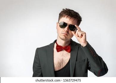 Portrait of a guy model. Sleazy, untidy, sexy man in a suit and a red bow tie. Naked, hairy chest, in sunglasses, on a gray background. Studio photo.