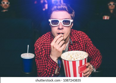A portrait of guy sitting in chair in cinema hall and eating popcorn. He is looking straight very intensive. Guy wears special glasses for watching 3d movies. Also he is eating popcorn from basket.