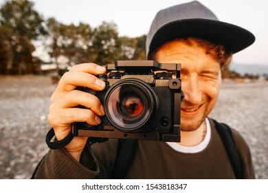 Portrait of a guy taking a photo with a professional camera. Close up portrait of photographer taking pictures with digital camera High Dynamic Range tone